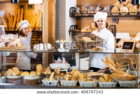 Helpful bakery staff offering bread and different pastry for sale - stock photo