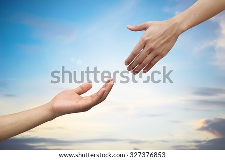 helping hand and hands praying on blurred beautiful sunrise sky backgrounds. helping hand concept.hand of god giving the power to human's. - stock photo