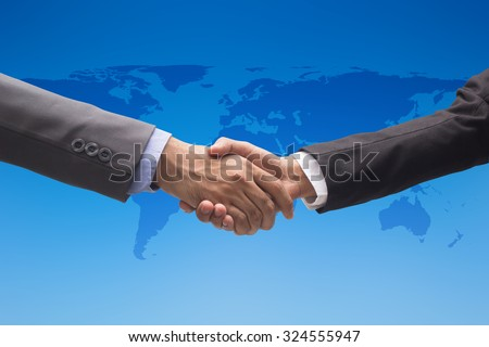 helping hand and handshake over blur map of the world on blurred blue sky backgrounds. helping hand concept.international assistance concept.business concept.peaceful concept.help economics crisis. - stock photo