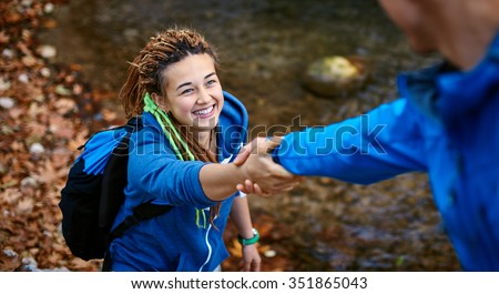 Helping hand - hiker woman getting help on hike smiling happy overcoming obstacle. Tourist backpackers walking in autumn forest. Young couple traveling. - stock photo