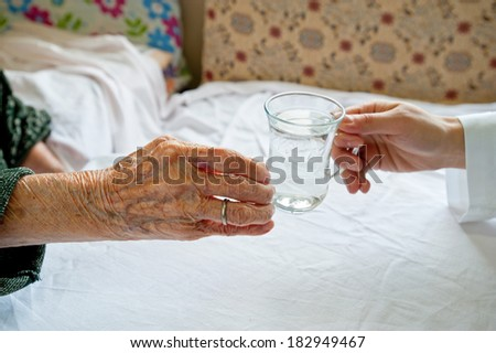 Helping hand. Nurse helping elderly woman - stock photo