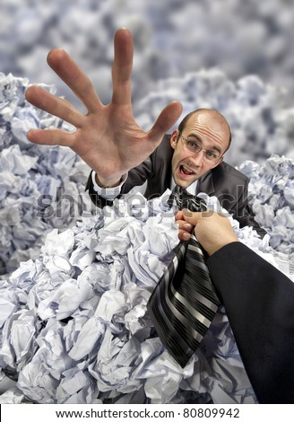 Helping hand saving businessman buried in big heap of crumpled papers - stock photo