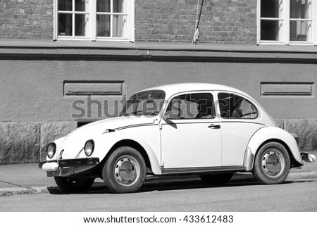 Helsinki, Finland - May 7, 2016: Old yellow Volkswagen beetle is parked on a roadside, black and white - stock photo