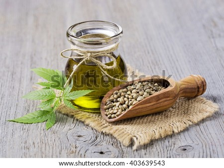 Hemp oil n a glass jar and hemp seeds - stock photo