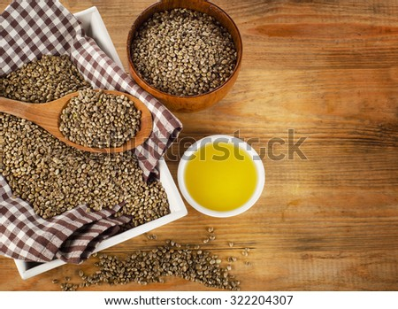 Hemp seeds and hemp oil on wooden background. Top view - stock photo