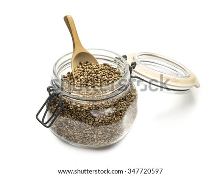 Hemp seeds in a glass jar with a wooden spoon on a white background - stock photo