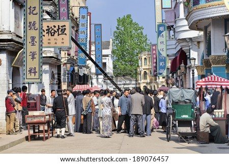 HENGDIAN-CHINA-APRIL 14, 2014. Film set with extras at Hengdian World Studios. With 495,995 sq. meter the largest movie town in Asia, construction began mid-1990s and has been ongoing ever since. - stock photo