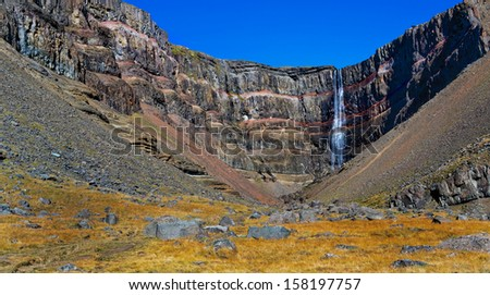 Hengifoss is the second highest waterfall on Iceland. The most special thing about the waterfall are multicolored layers in the basalt rock. - stock photo