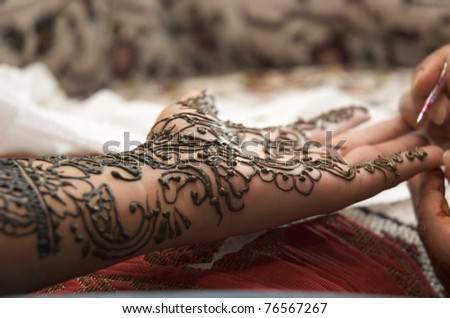 Henna being applied to hand of an Indian bride - stock photo