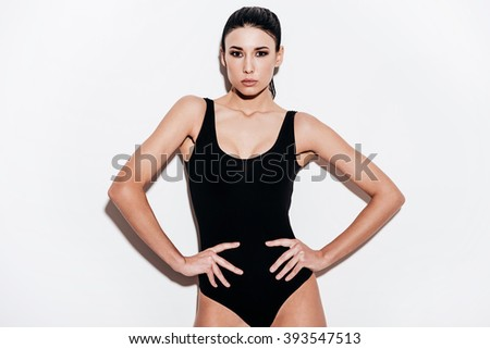 Her beauty is stunning. Beautiful young woman in black swimsuit holding hands on hips and looking at camera while standing against white background - stock photo