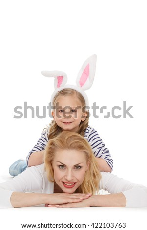 Her biggest support. Portrait of a little charming girl lying on the back of her mother on top of her looking to the camera smiling isolated on white.   - stock photo