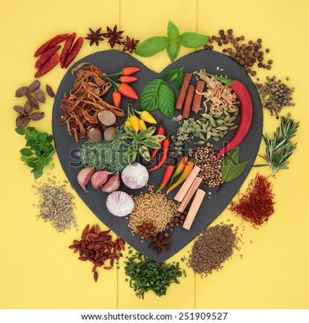 Herb and spice ingredients on a heart shaped slate and loose over yellow wooden background. - stock photo