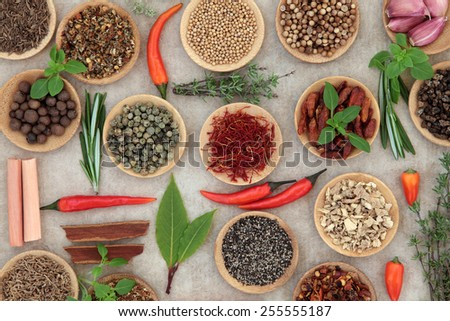 Herb and spice selection in wooden bowls and loose over grunge paper background. - stock photo