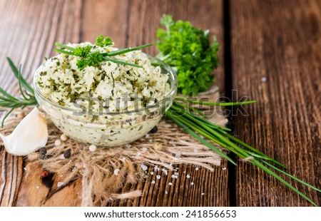 Herb Butter in a small bowl (on wooden background) - stock photo