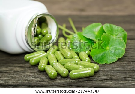 Herb capsule spilling out of a bottle. - stock photo