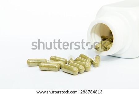 Herb capsule spilling out of bottle isolated on white background - stock photo