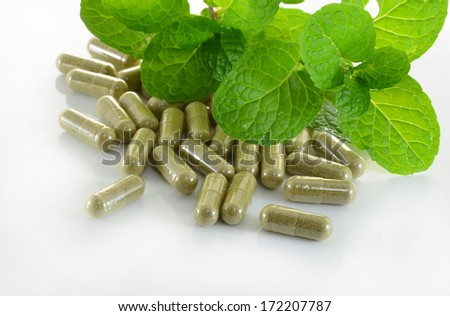 herb capsule with green herbal leaf - stock photo
