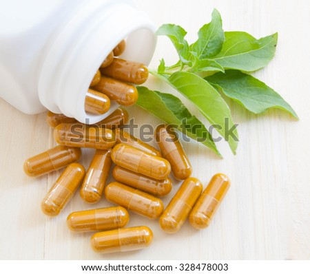 herb capsules spilling out of a bottle - stock photo