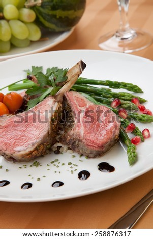 Herb crusted lamb chops (ribs) garnished with asparagus, carrots, and pomegranates. Mini pumpkins and fresh fruits