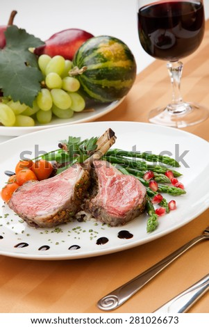 Herb crusted lamb chops (ribs) garnished with asparagus, carrots, and pomegranates. Mini pumpkins and fresh fruits  - stock photo