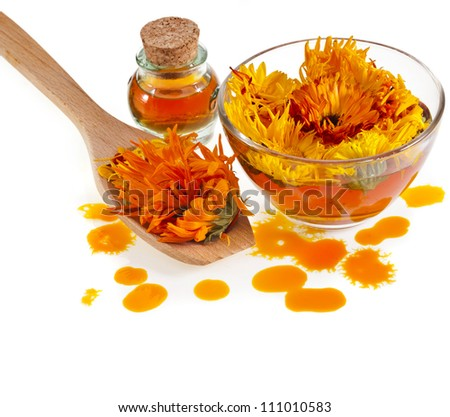 herbal calendula in the glass and drop oil Isolated white background - stock photo