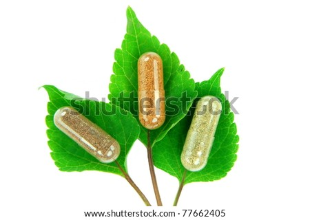 herbal capsules on melissa leaves - stock photo