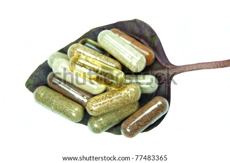 Herbal capsules on red basil leaf - stock photo