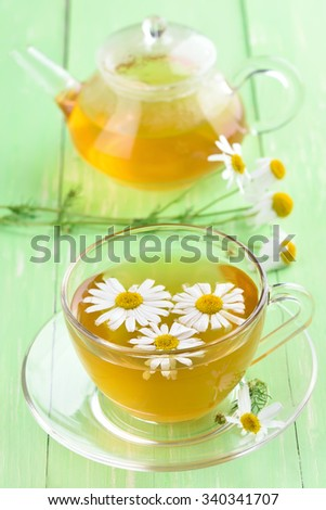 Herbal chamomile tea in glass cup on green table - stock photo