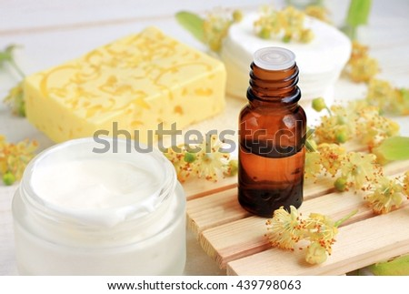 Herbal cosmetic products. Tilia tree (lime blossom) ethereal oil bottle, fresh facial cream, yellow soap bar. - stock photo