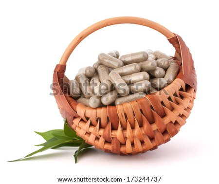 Herbal drug capsules in wicker basket isolated on white background cutout. Alternative medicine concept. - stock photo