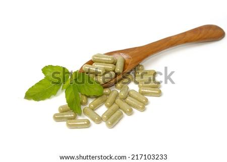 Herbal drug capsules in wooden spoon . Alternative medicine concept. - stock photo