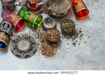 Herbal green tea with cardamom and rose flower petals. Oriental table decoration - stock photo