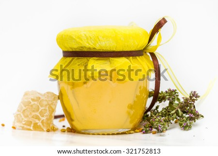 Herbal honey in jar with small honeycomb and herbs isolated on white background - stock photo