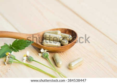 Herbal medicine in capsules with herb on wooden spoon  - stock photo