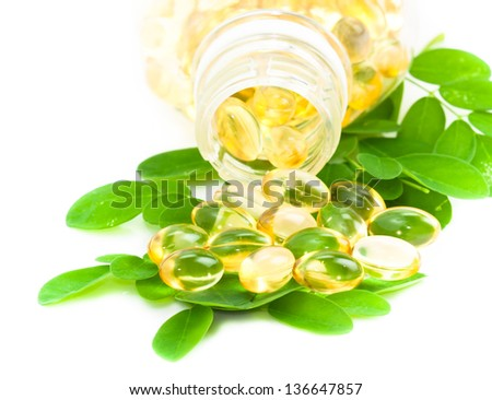 herbal medicine oil pills with green plant on white background - stock photo