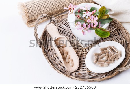 Herbal medicine pills and hawthorn flowers on a woven tray over white background. Selective focus, copy space - stock photo