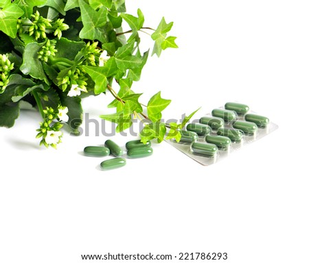 herbal medicine pills with green plant on white background. alternative therapy concept - stock photo
