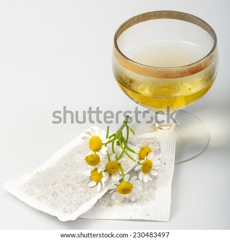 Herbal medicine series: Chamomile flowers, glass of tea and teabags on white background - stock photo