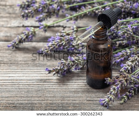Herbal oil essence and dried lavender flowers on wooden background. Alternative home medicine. Selective focus - stock photo