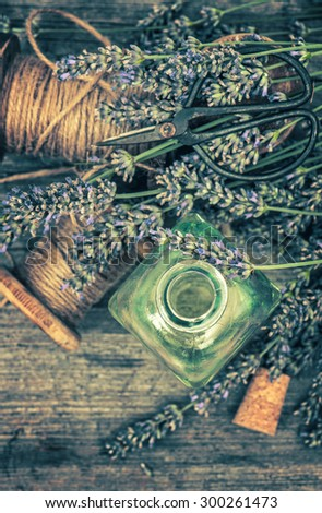 Herbal oil essence and lavender flowers. Vintage decoration. Top view. Retro style toned picture. Selective focus - stock photo