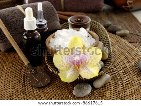 herbal salt in bowl and orchid with stones and massage oil on burlap texture - stock photo