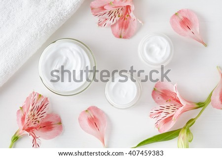 Herbal spa cosmetic cream with pink flowers hygienic skincare lotion product wellness and relaxation makeup mask in glass jar with towel on white background - stock photo