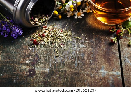 Herbal tea and wild organic flowers on wooden background - stock photo