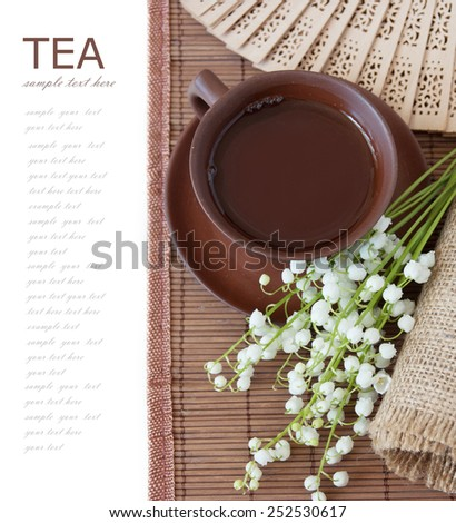 Herbal tea (cup of tea, lily of valley, fan on bamboo mat isolated on white background with sample text) - stock photo