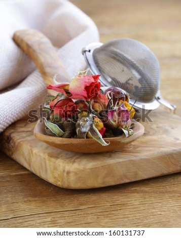herbal tea from the dried flower buds of roses in a wooden spoon - stock photo