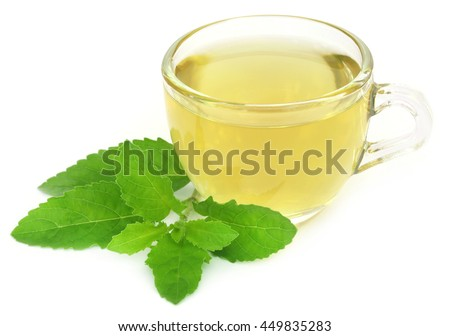 Herbal tea in a cup with tulsi leaves over white background - stock photo