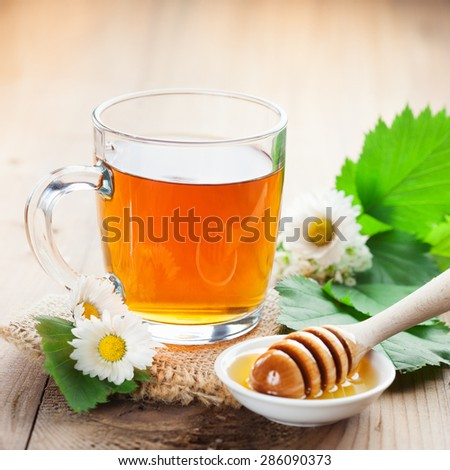 Herbal tea in a glass bowl with camomile flowers and honey on rustic wooden background, selective focus - stock photo
