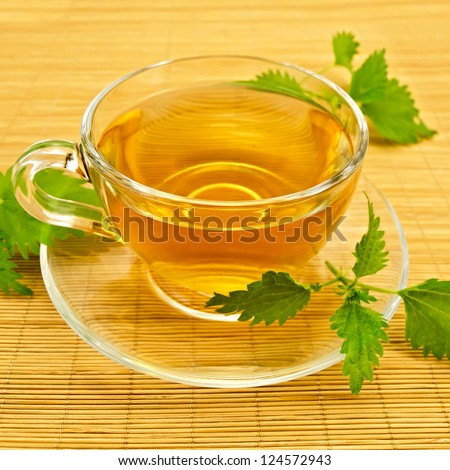 Herbal tea in a glass cup and saucer, three twig nettle on a bamboo napkin - stock photo