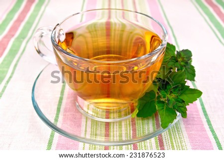 Herbal tea in a glass cup, fresh mint leaves on a background of striped linen tablecloths - stock photo