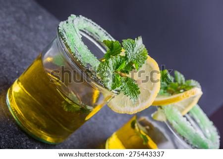 Herbal Tea with a fresh lemon balm leaves on a black table - stock photo